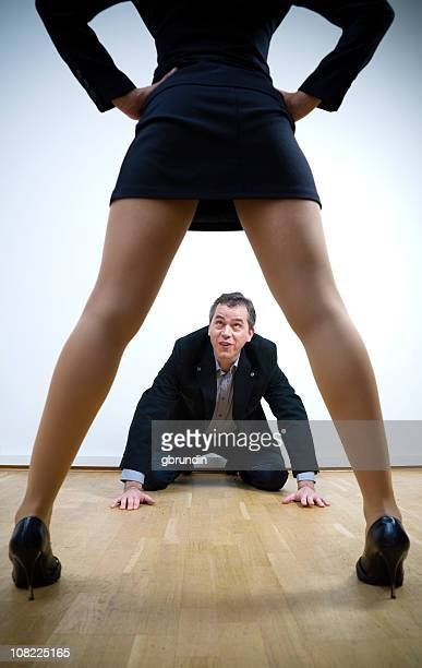 man on hands and knees with woman standing above him - legs apart stock photos and pictures