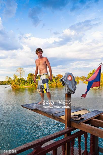 A man on high plank dives into the Mekong.