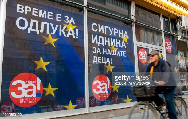 A man on his bicycle passes past campaign posters reading For a European Macedonia in a street of Skopje on September 29 Voters across the Balkan...