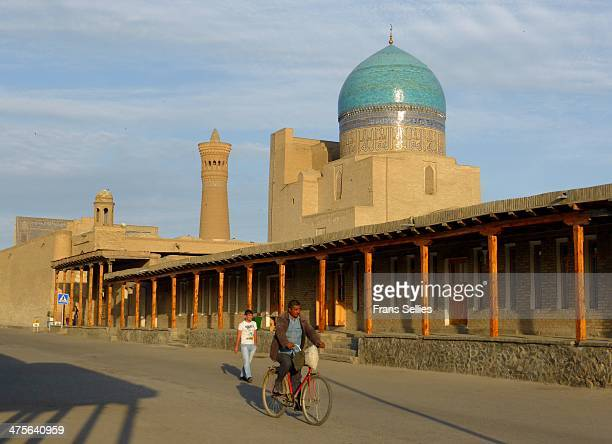 Man on his bike at the Kalon mosque in Bukhara. The historic center of Bukhara, which contains numerous mosques and madrassas, has been listed by...