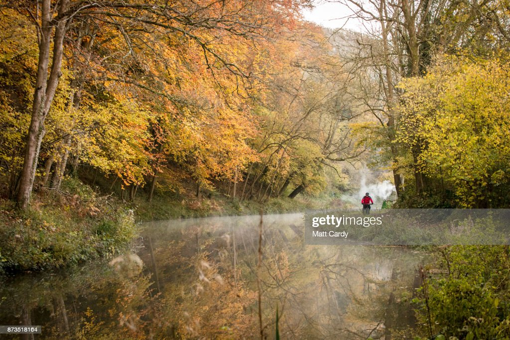 A man on his bike passes the autumn colours from the trees reflected in the water of the Kennet and Avon canal near the Dundas Aqueduct as the sun rises on November 13, 2017 near Bath, England. After a warm autumn, with temperatures above average, much colder weather has arrived in many parts of the UK, signalling the start of more wintery weather for the coming few weeks.