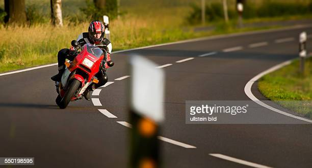 Man on his Ducati in a curve on a rural road
