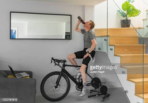 man on his turbo trainer at home. - shorts stock pictures, royalty-free photos & images