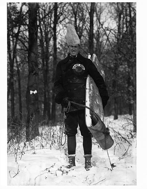 A man on his way to the St Paul Winter Carnival pauses in St Anthony Park with his sled