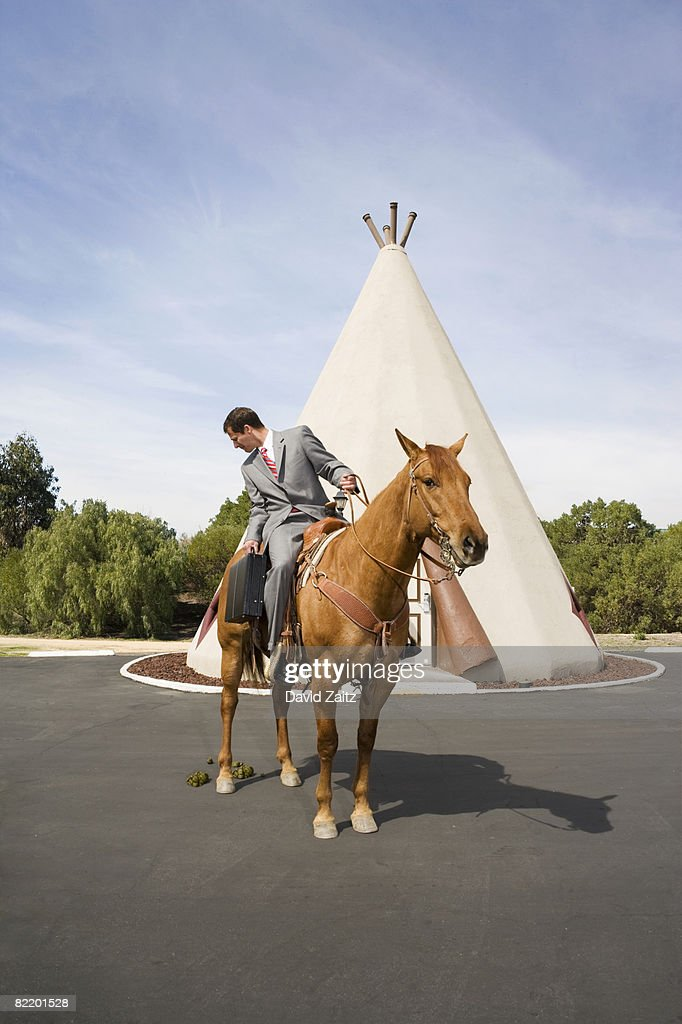 Man on horse in front of tepee-shaped motel unit. : Stock Photo