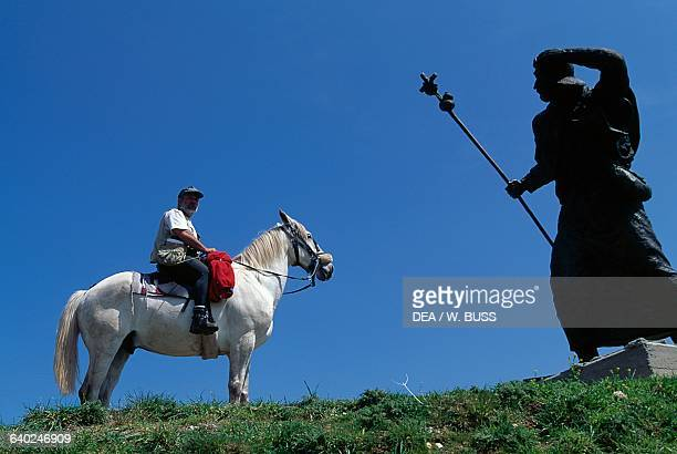 Man on horseback near the bronze pilgrim statue near Alto de San Roque on the Way of St James of Compostela Galicia Spain