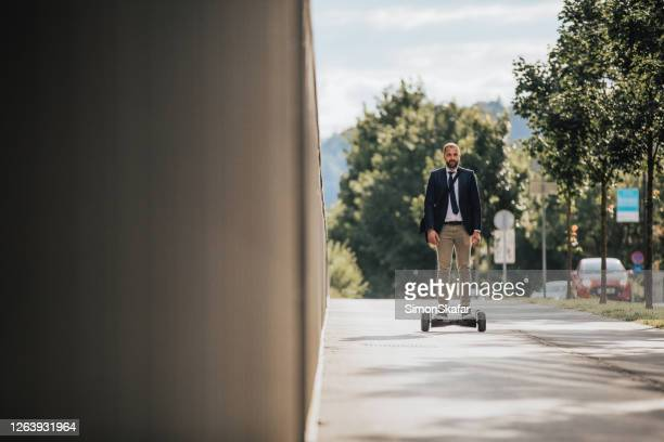 man on hoverboard - hoverboard stock pictures, royalty-free photos & images