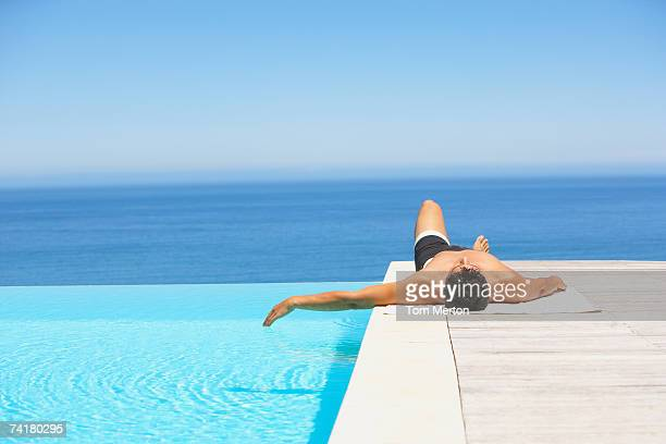 Homme sur la terrasse de la piscine à débordement en maillot de bain