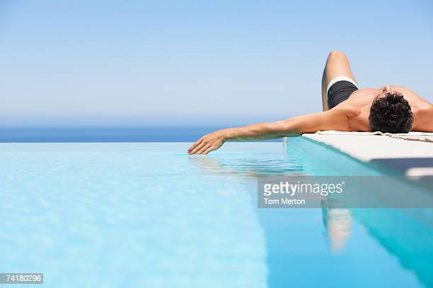 man on infinity pool deck in swimsuit - zwembroek stockfoto's en -beelden