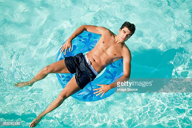 man on inflatable ring in pool - badkleding stockfoto's en -beelden