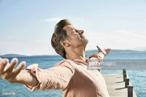 man on jetty enjoying sunlight - hair stubble stock pictures, royalty-free photos & images