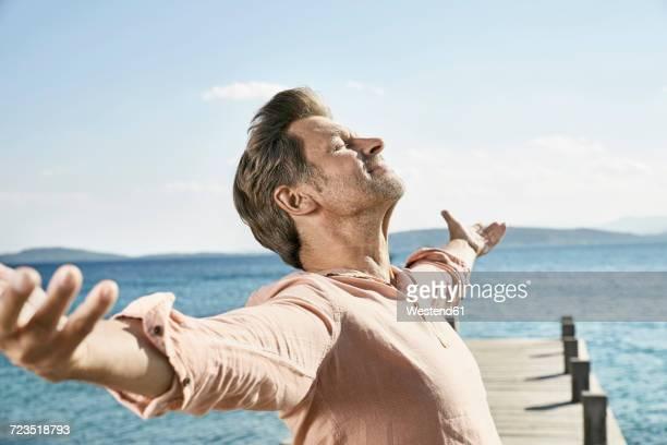 man on jetty enjoying sunlight - barba por fazer imagens e fotografias de stock