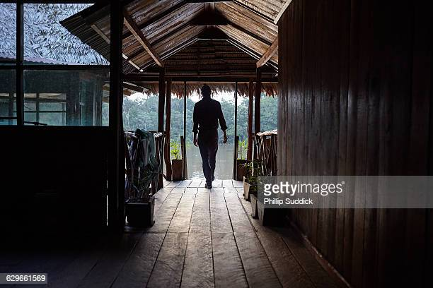 man on jetty overlooking jungle river in hut