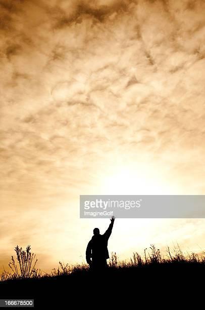 Hombre en las rodillas en elogios y de culto silueta
