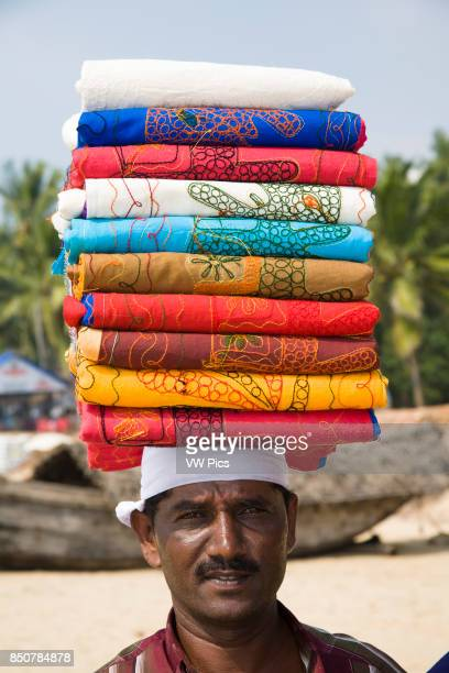 Man on Kovalam Beach carrying tablecloths on his head Kovalam Kerala India