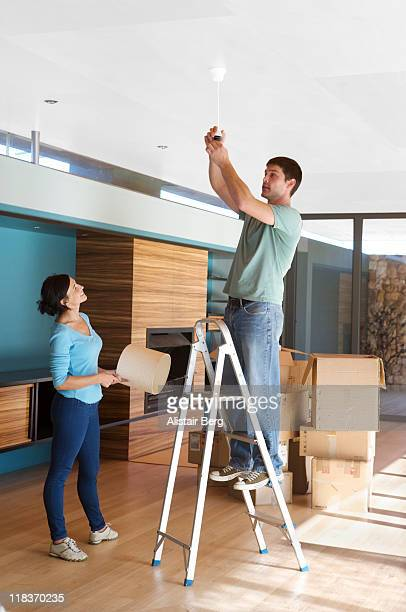 man on ladder changing lightbulb - step ladder stock pictures, royalty-free photos & images