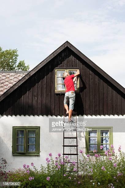man on ladder repairing window - sforzo foto e immagini stock