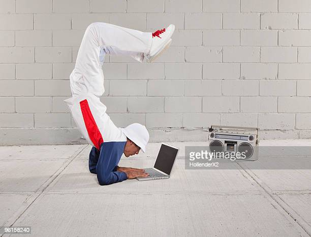 man on laptop while in yoga/breakdancing pose