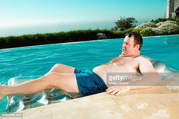 man on lilo - chubby swimsuit stock photos and pictures
