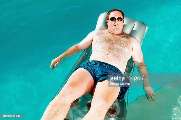 man on lilo - chubby men stock photos and pictures
