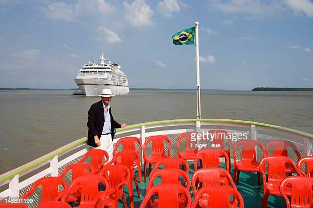 Man on local transfer boat, cruiseship MS Europa (Hapag-Lloyd Cruises) in background.