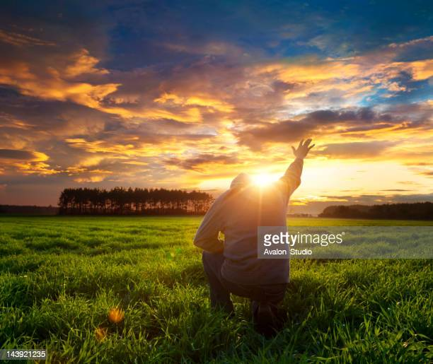 Man on meadow praying to god facing the sun