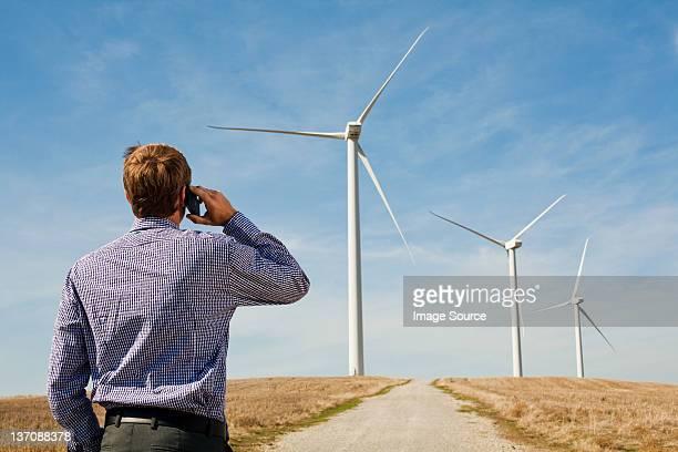 Man on mobile phone watching wind turbines