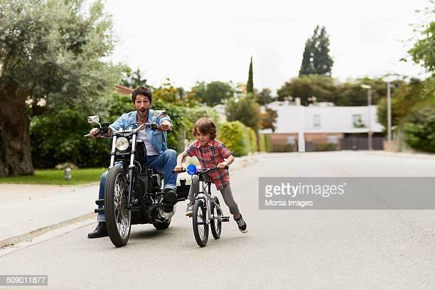 Man on motorbike chasing son riding bicycle