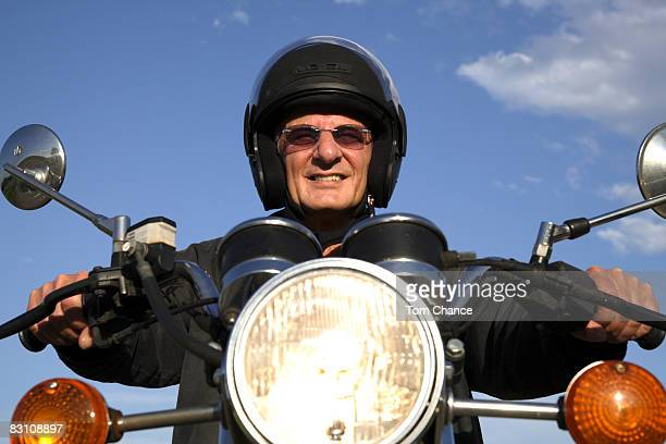 Man on motorbike, smiling, portrait