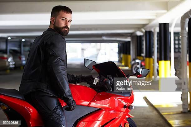 man on motorcycle in garage - calça comprida - fotografias e filmes do acervo