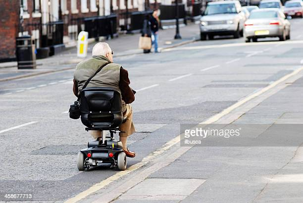 man on motorized chair in the streets of liverpool - mobility scooter stock photos and pictures