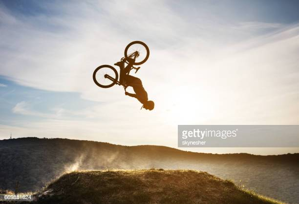 man on mountain bicycle performing backflip in nature. - bmx cycling stock pictures, royalty-free photos & images