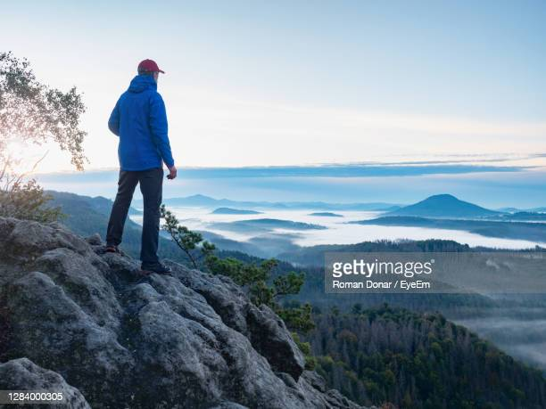 man on mountain peak look on mountain valley in early autumn. landscape with traveler, foggy hills - look back at early colour photography imagens e fotografias de stock