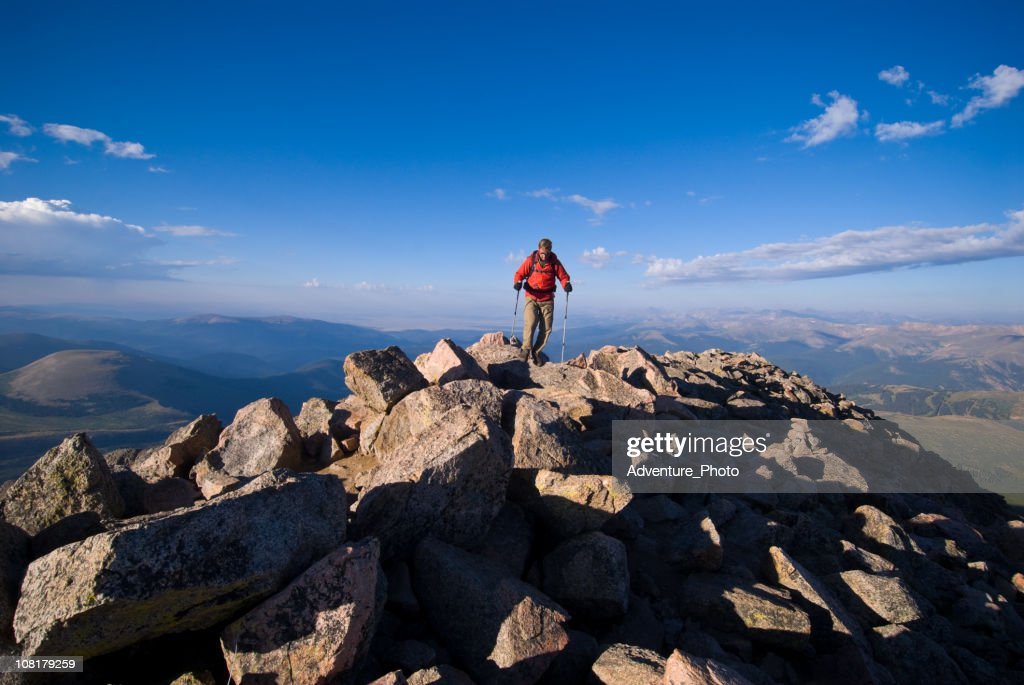 Man on Mountain Summit Peak Hiking High in Rocky Mountains : Stock Photo