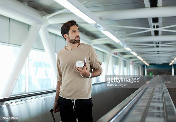 man on moving walkway at airport