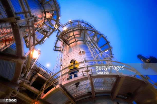 Man on oil refinery distillation tower