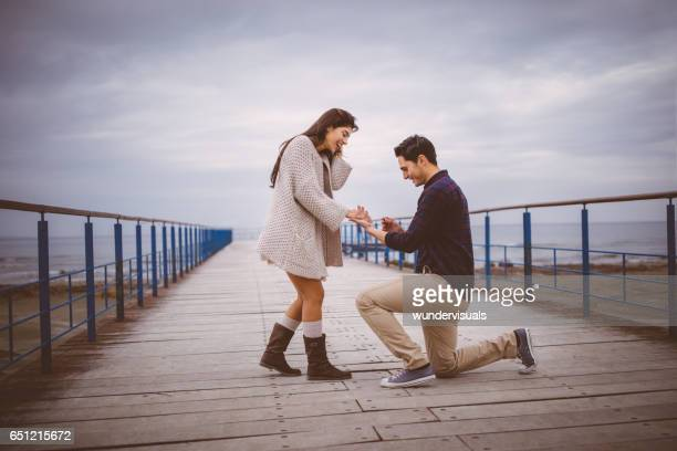 Man on one knee proposing to girlfriend on a pier