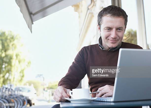 man on outdoor patio with laptop - flexplekken stockfoto's en -beelden
