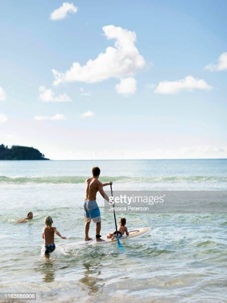 man on paddleboard with his children at beach - hawaii islands stock pictures, royalty-free photos & images