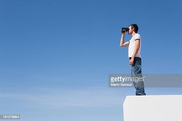 Mann auf Sockel mit Fernglas und blauer Himmel im Freien