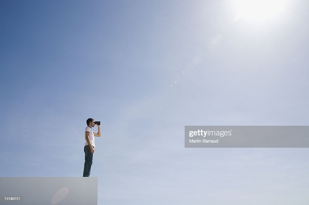 Man on pedestal with binoculars and blue sky outdoors : Stock Photo