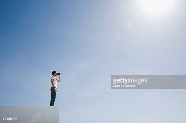 man on pedestal with binoculars and blue sky outdoors - ver stockfoto's en -beelden