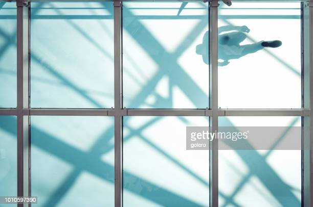 man on pedestrian glass bridge - man made structure stock pictures, royalty-free photos & images
