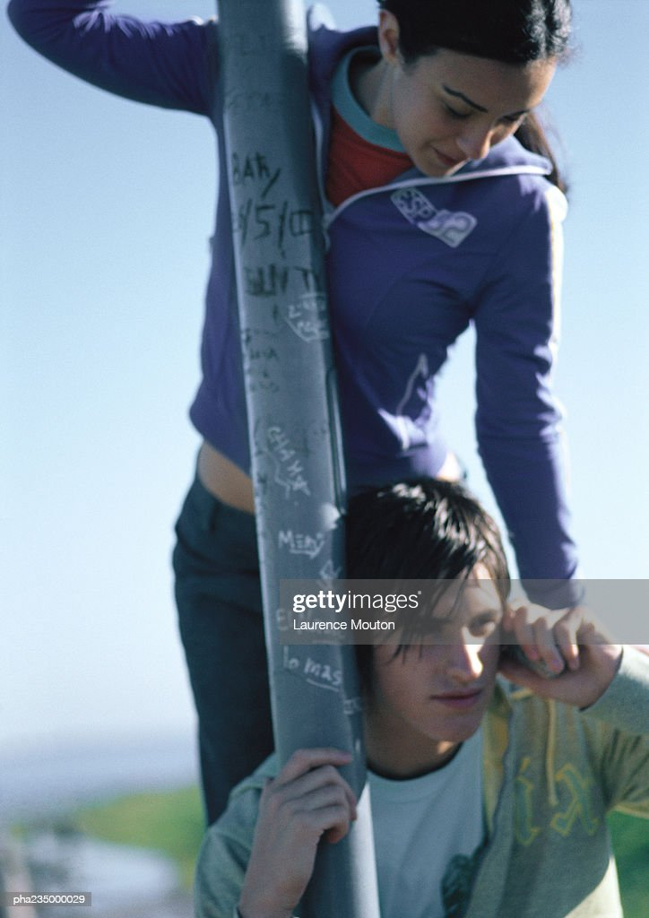 Man on phone holding onto a pole with woman standing above him. : Stockfoto