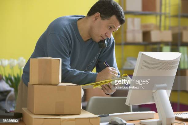 man on phone in shipping department looking at computer screen and writing on legal pad - dominican ethnicity stock photos and pictures