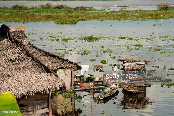 Man on pier at home on Amazon river, Iquitos, Peru.