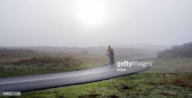 man on racing bicycles cycling in wintry landscape