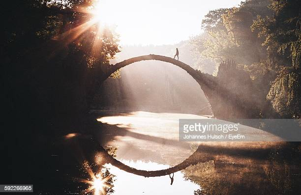 man on rakotz bridge over lake with reflection in park - symmetry stock photos and pictures