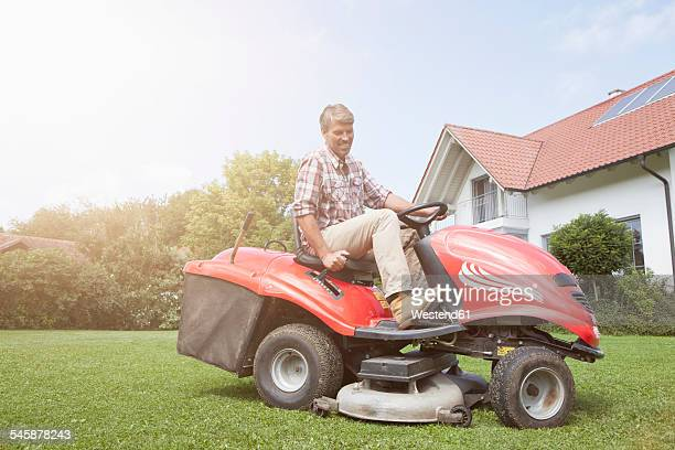 Man on riding lawn mower in garden