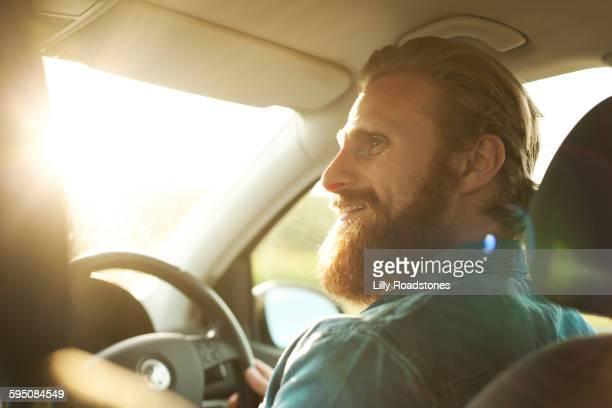 man on roadtrip driving car - vollbart stock-fotos und bilder